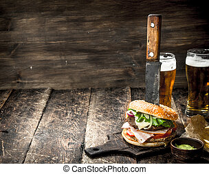 Street food. A big burger with beer.