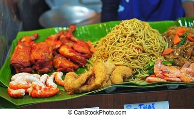Street food at asian night market - noodle, fried chicken, shrimps on sale for travelers