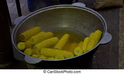Street food. Cooking corn in boiled water. Sweet corn...