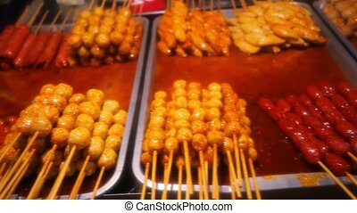 Street food in Thailand - fried sausages, meatballs and chicken