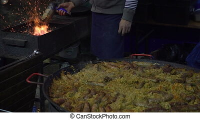 Street food. Man cooks and bakes delicious grilled sausage.