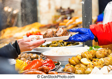 Street food market - Hands of vendor giving food on street...