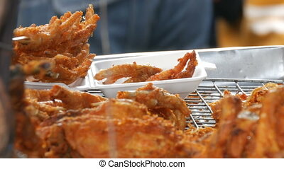 Street food of Thailand. Fried chicken pieces in batter.The seller on the street is selling an exotic dish. The buyer selects a piece of meat with the help of special tongs for food