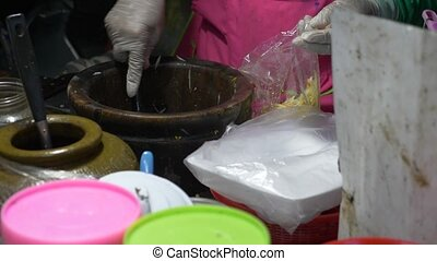 street food, Thailand. the cook prepares a traditional Thai...