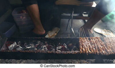 Street food hawker selling charcoal grilled satay, meat on skewers. delicious
