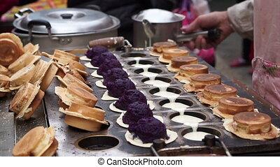 Street food vendor in Taiwan, ROC. Cooking flour stuff with purple yam