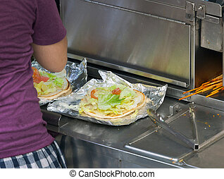 Street food vendor prepares a flat bread with salad and...