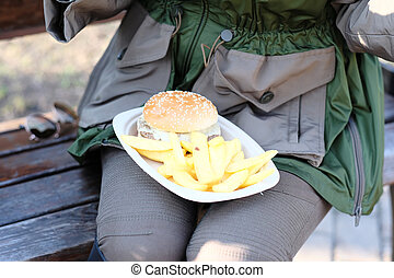 Street food. Woman holding hamburger and french fries...