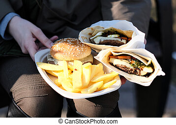 Street food. Woman holding hamburgers and french fries...