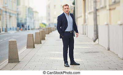Street full length portrait of middle aged man wearing blue suit.