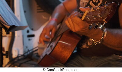 Street Guitarist Plays Acoustic Guitar at Night in the Light...