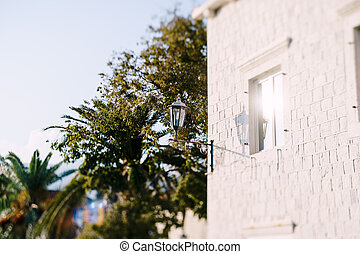 Street hanging lamp on a house on a sunny day. Perast town in Montenegro.