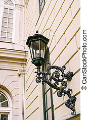 Street hanging lamp with a beautiful bracket in the wall of a multi-storey building.