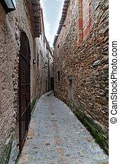 Street in Peratallada, Spain - Narrow passageway between two...