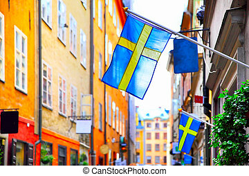Street in Stockholm with swedish flags - Old street in...