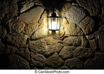 Street lamp illuminates the stone wall at night