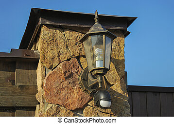 Street lamp in retro style, with a light sensor, on a pillar made of natural stone.
