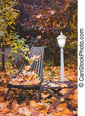 Street lamp on a background of autumn leaves.