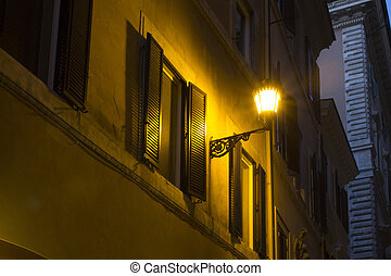 Street lamp on a historical, old building in Rome at night.