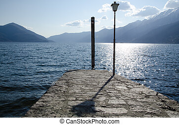 Street lamp on a pier close to a lake with mountains