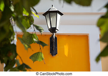 street lamp on a yellow wall framed by leaves