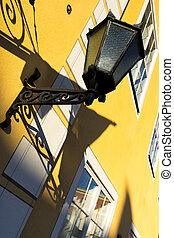 Street lamp on a yellow wall with windows