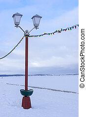 Street lamp on embankment of frozen lake