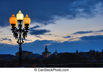 Street lamp on the background of a beautiful sunset sky with clouds. Colorful houses and church