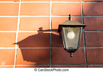 Street lamp over red brick wall