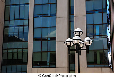 Street lamp post against glass building background
