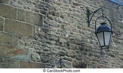 Street lamp swinging in the wind on a background of a stone wall in an ancient temple