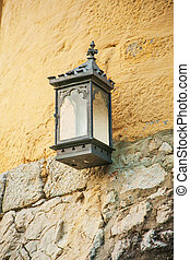 street lamp with a candle attached to the outside of the house