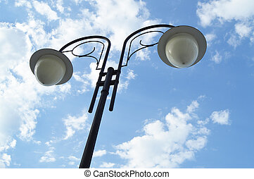 Street lamp with shades on a background of blue sky and clouds