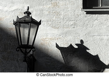 Street lamp with shadow on wall