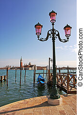 Vertical oriented image of street lamppost and Grand Canal in Venice, Italy.