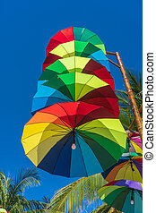Street lamps decorated with colorful umbrellas hang on a pillar in street against the blue sky and coconut palm tree on a sunny day