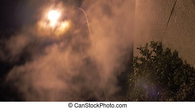 Street lantern and condensing smoke spreading outside at...