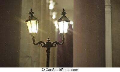 Street lanterns in the snow at night