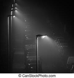 Modern LED street lights illuminating an empty foggy street, spider web on the lamp, square crop
