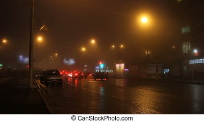 Street lights of city in fog and cars on road.