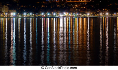 Street lights reflection over sea at night, timelapse -...