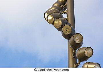 Street lights shot close up against the sky.