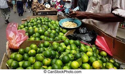 Street Lime Vendor Peels Fruit For Display and Sampling.