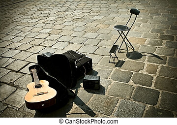 Guitar and chair waiting the musician, in street