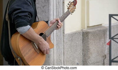 Street musician playing on acoustic guitar. Slow Motion -...