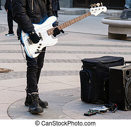 Street musician playing on electric guitar. Unrecognizable...