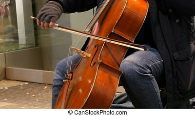 Street musician playing the cello. Cellist in gloves gently...
