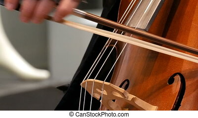 Street musician playing the cello close up view. Cellist in gloves gently bows strings