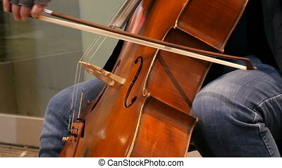Street musician playing the cello close up view. Cellist in...