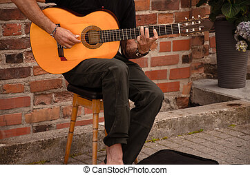 Street musician playing with guitar in Vilnius street, ...